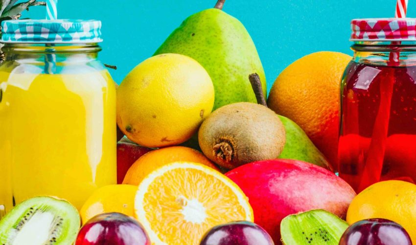 fresh-healthy-fruits-juice-mason-jars-table-against-blue-background-compressed